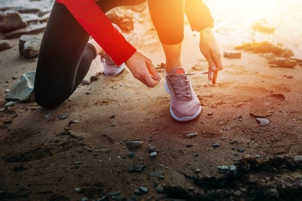 Unrecognizable Athletic Young Woman Tying Shoelaces Near The Sea Unrecognizable Athletic Young Woman Tying Shoelaces Near The Sea, While Pausing During Exercises biohacking stock pictures, royalty-free photos & images