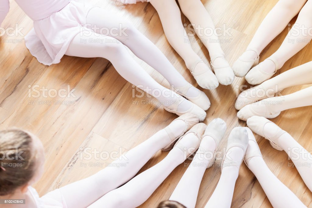 Unrecognizable ballerinas sit in a circle with their feet together stock photo