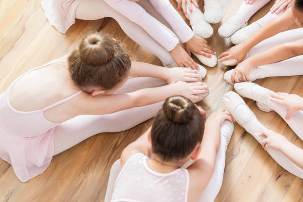 Unrecognizable ballerinas sit with their feet together while touching toes stock photo