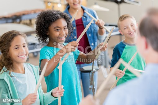 An unrecognizable band teacher stands in front of an attentive group of elementary age children and teaches drumming.  The smiling children look at him and each hold a pair of drumsticks up in the air.
