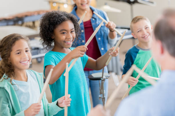 Unrecognizable band teacher teaches drumming to students stock photo