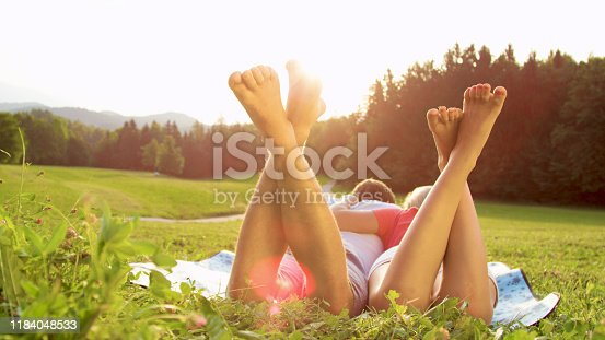 CLOSE UP SUN FLARE: Unrecognizable barefoot man and woman lie in the serene countryside and enjoy a romantic date. Young boyfriend and girlfriend lying embraced on a blanket in the sunlit meadow.