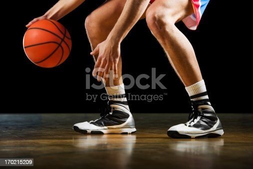 Basketball player is dribbling on the basketball court.