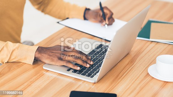 Copywriter. Close up afro businessman writing content on notebook, using laptop at wooden table at office, panorama