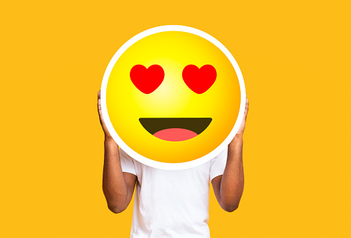 istock Unrecognizable black man hiding face against in love emoticon emoji 1269074722