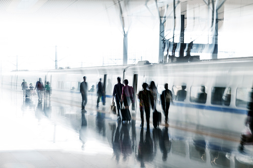 Unrecognizable, blurred passengers getting on a train