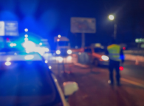 istock Unrecognizable blurry police car lights and police force officer on night road background, crime scene, night patrolling the city. Abstract  defocused image. 1084565926