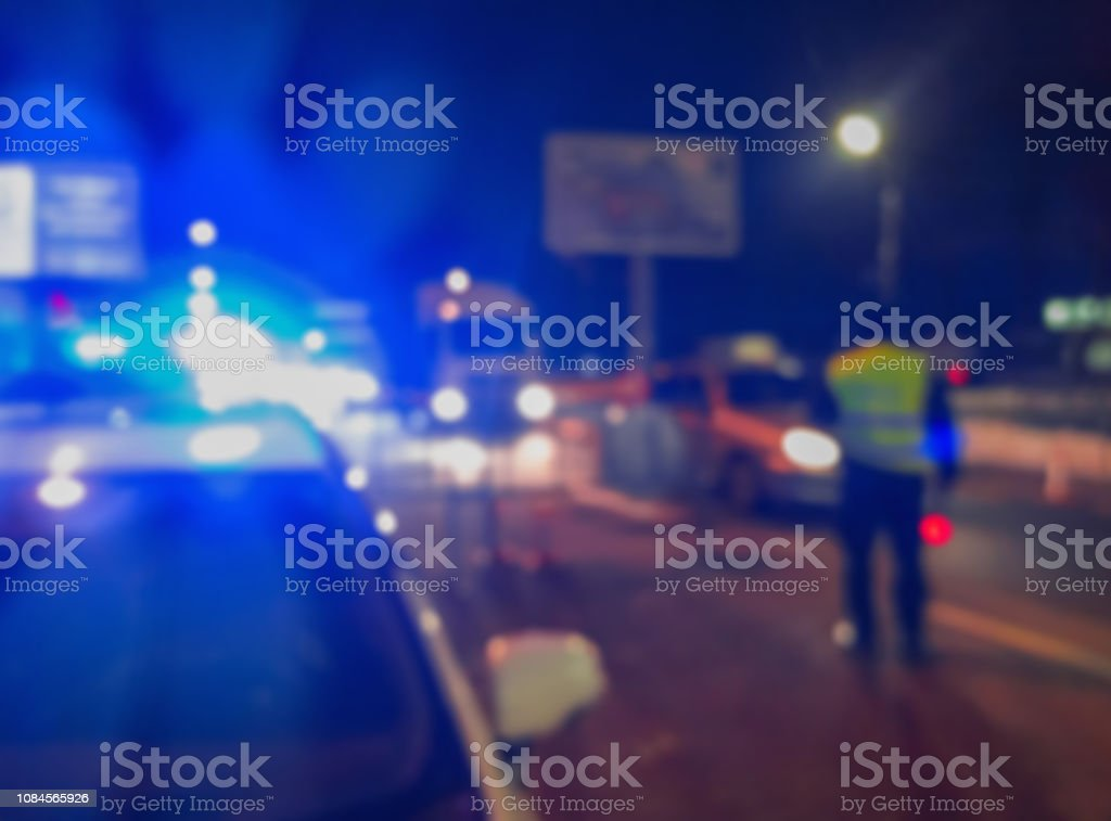 Feux de voiture de police floue méconnaissable et officier de la force de police sur fond de route de nuit, scène de crime, la nuit alors qu'ils patrouillaient la ville. Image défocalisé abstraite. - Photo