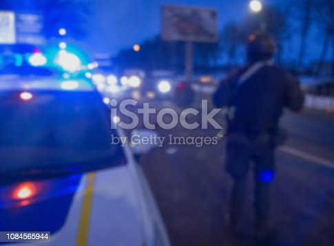istock Unrecognizable blurry police car lights and police force officer on night road background, crime scene, night patrolling the city. Abstract  defocused image. 1084565944