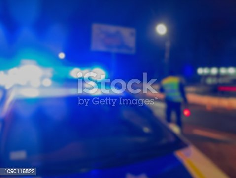 istock Unrecognizable blurry police car lights and police force officer on night road background, crime scene, night patrolling the city. Abstract  defocused image. 1090116822