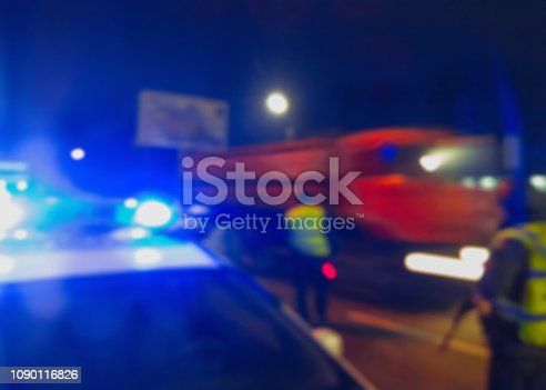 istock Unrecognizable blurry police car lights and police force officer on night road background, crime scene, night patrolling the city. Abstract  defocused image. 1090116826