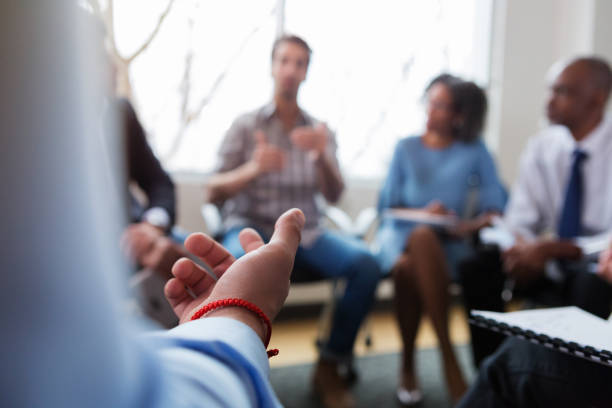 Unrecognizable business person gestures during meeting An unrecognizable businessperson gestures during a meeting. Only the businessperson's arm and hand are seen in the photo. group therapy stock pictures, royalty-free photos & images
