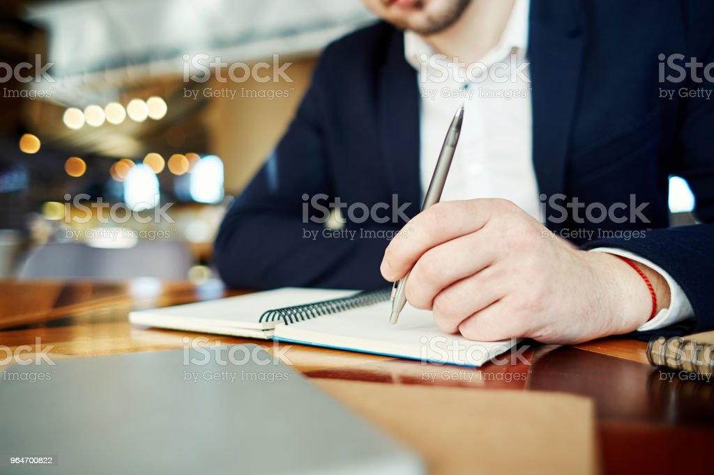 Unrecognizable businessman holding pen in his hand and thinking over notes in his notebook royalty-free stock photo