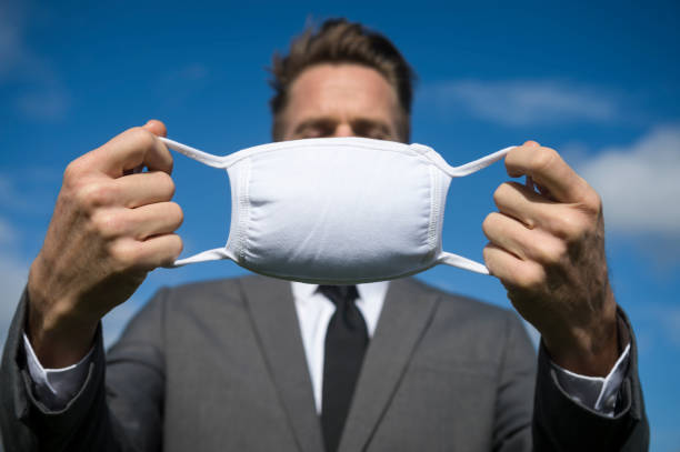 Unrecognizable Businessman Holding Surgical Face Mask Outdoors stock photo