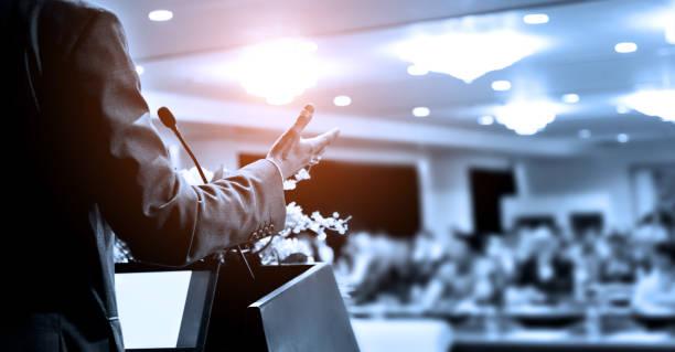 Unerkennbarer Geschäftsmann hält eine Rede vor Publikum im Konferenzsaal – Foto