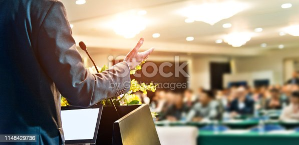 Unrecognizable businessman making a speech in front of audience at conference hall.