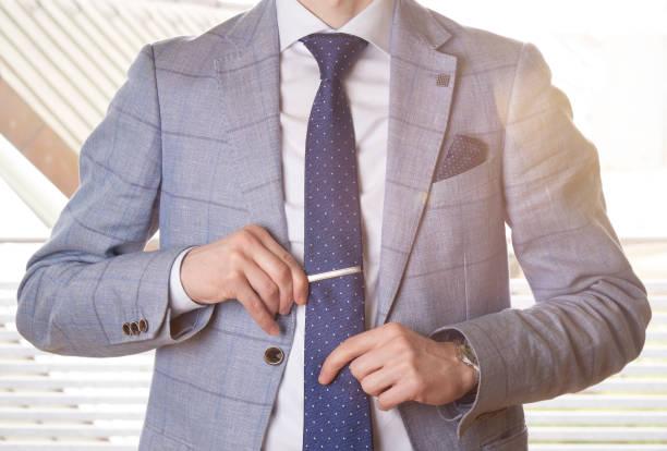 nicht erkennbare geschäftsmann einstellung die krawatte gerade durch die anpassung seiner krawattennadel. hintergrundbeleuchtung mit ein lens-flare-effekt. - krawattennadel stock-fotos und bilder