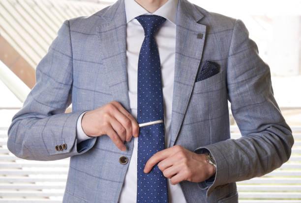 nicht erkennbare geschäftsmann die krawatte gerade einstellen - krawattennadel stock-fotos und bilder