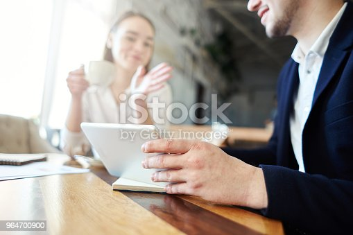 Unrecognizable Businessman Showing Presentation On Tablet Computer To Female Business Partner During Coffee Meeting In Cafe Stock Photo & More Pictures of Adult