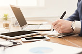 Unrecognizable businessman typing on laptop