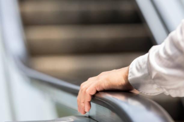 unrecognizable businessman using escalator - escalator foto e immagini stock