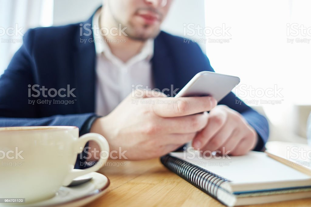 Unrecognizable businessman using smartphine while sitting at table in cafe. Coffee cup and open notebook in front of him royalty-free stock photo