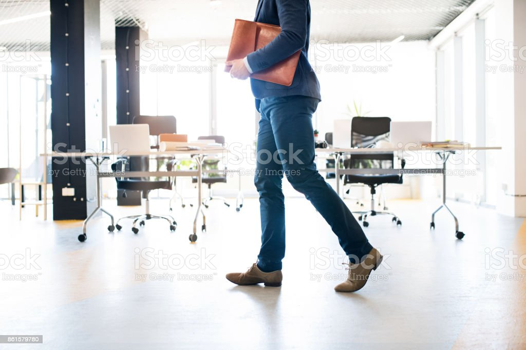 Unrecognizable businessman walking in an office. stock photo