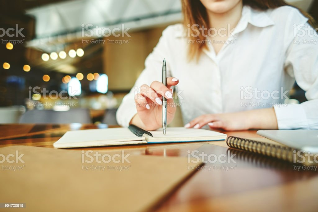 Unrecognizable businesswoman holding pen in her hand and thinking over notes in notebook while sitting at table in cafe royalty-free stock photo