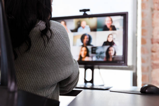 Unrecognizable businesswoman participating in virtual staff meeting stock photo