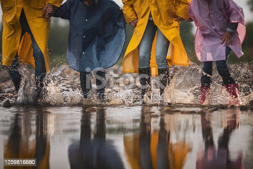 Unrecognizable family in raincoats having fun while stepping into big puddle in nature. Copy space.