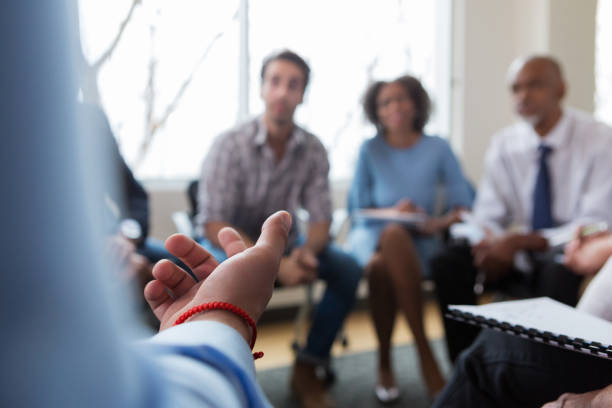 Unrecognizable Caucasian person gestures while speaking As the diverse team of professionals looks on, an unrecognizable Caucasian team member speaks and gestures. staff meeting stock pictures, royalty-free photos & images