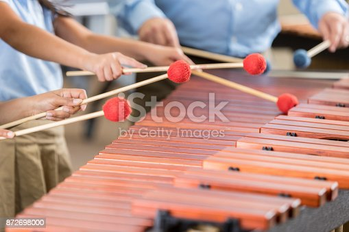 In this closeup, all are unrecognizable as two elementary band students stand next to their teacher and play the xylophone with him.