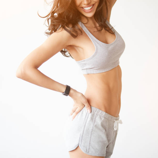 unrecognizable closeup of fitness female smiling and showing her body - corpo foto e immagini stock
