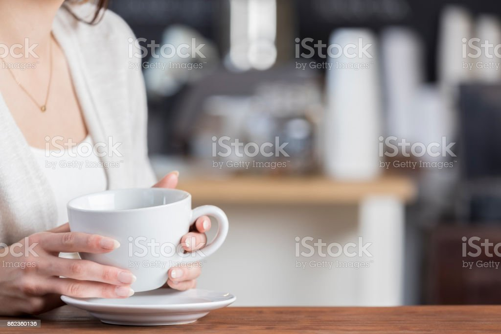 Unrecognizable coffee shop customer sits holding mug stock photo