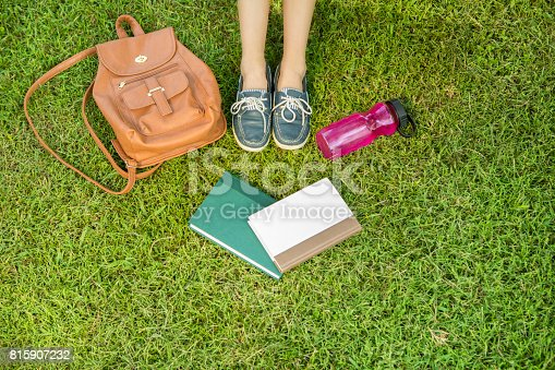 istock Unrecognizable college student sits in grass on campus 815907232