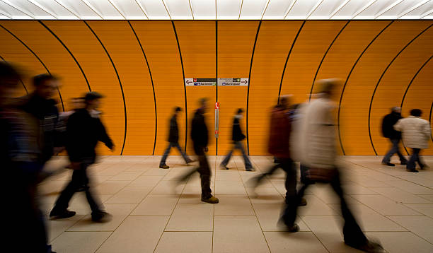 unrecognizable commuters at an orange underground - perpetual motion stock photos and pictures