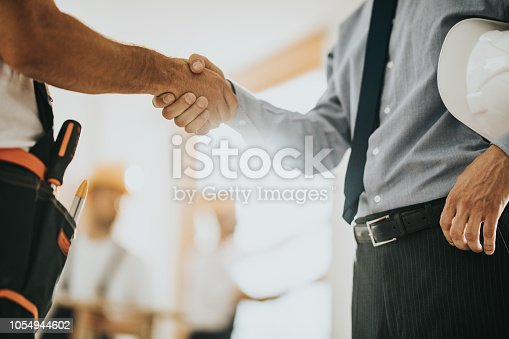 961745166istockphoto Unrecognizable construction worker greeting a foreman at renovating apartment. 1054944602