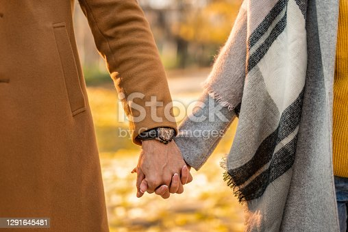 Hand close-up of unrecognizable couple holding hands in the park on autumn day.