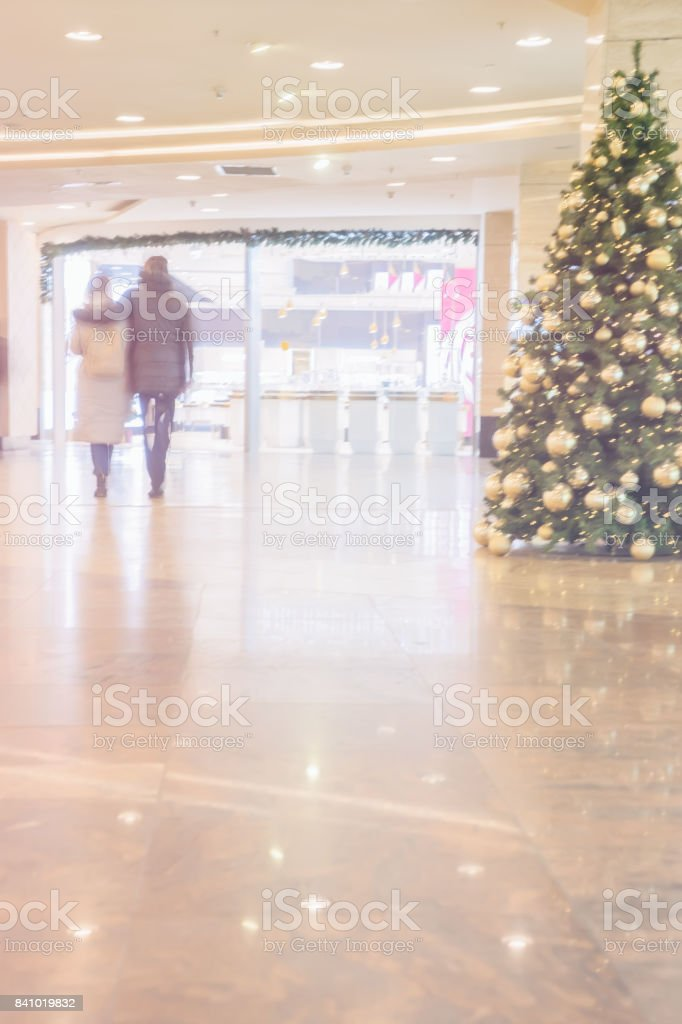 Unrecognizable couple in love walks through shopping center on pre-Christmas holidays. Abstract backdrop stock photo