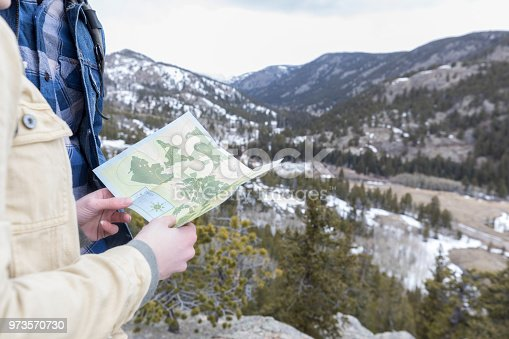 483422527istockphoto Unrecognizable couple looks at map during mountainous hike 973570730