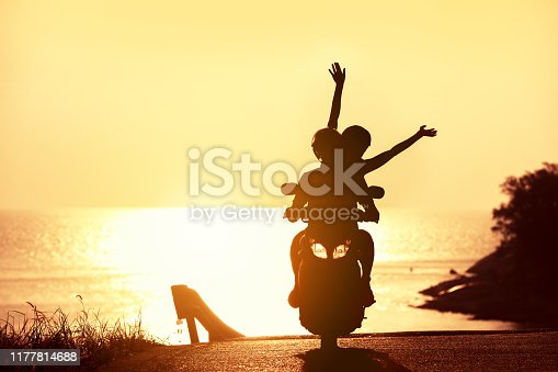 Unrecognizable couple with raised arms rides on scooter against sunset sea
