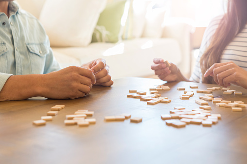 istock Unrecognizable couple play word game together at home 1165213506