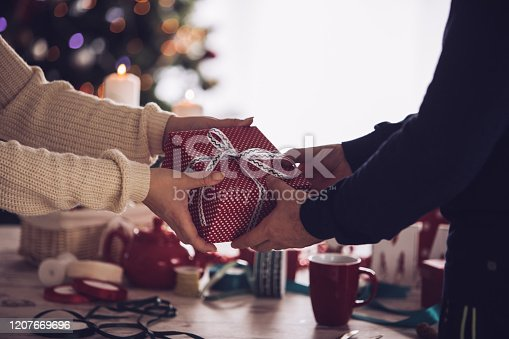 Shot of unrecognizable heterosexual couple sharing a beautifully wrapped Christmas gift in front of a rustic wooden table with ribbons and decoration.