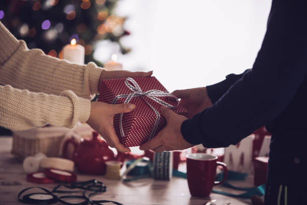 Unrecognizable couple sharing a Christmas gift stock photo