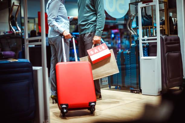 nicht erkennbare paar stehen am eingang eines taschen und accessoires store mit einem reise-koffer und einkaufstaschen - trolley kaufen stock-fotos und bilder