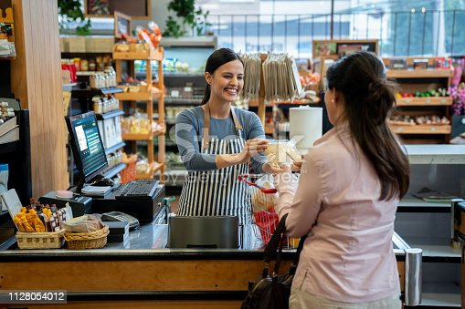 istock Unrecognizable customer at supermarket handing products to friendly cashier for checkout 1128054012