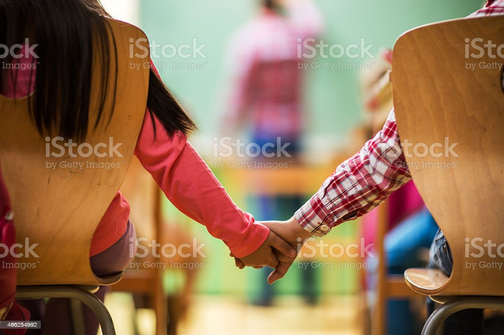 Unrecognizable elementary school children holding hands in the classroom. stock photo