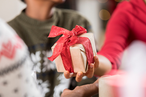An unrecognizable woman gives a gift to a family member on Christmas Day. Close up is on the present. The present is wrapped in gold wrapping paper and tied with a red bow.