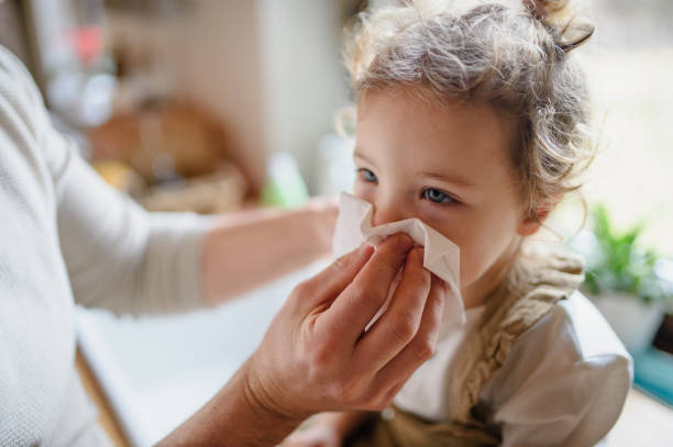Unrecognizable father blowing nose of small sick daughter indoors at home. stock photo