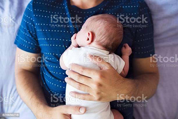 Unkenntlich Erkennbarer Vater Mit Seinem Neugeborenen Kleinen Sohn Im Bett Liegend Stockfoto und mehr Bilder von Vater